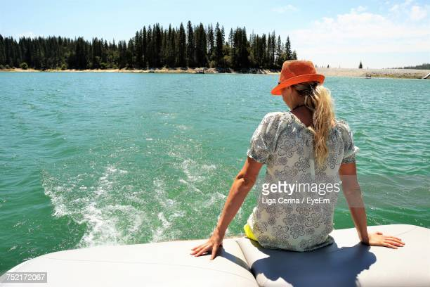 rear view of woman sitting on boat by lake on sunny day - liga cerina stock pictures, royalty-free photos & images