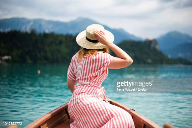 rear view of woman sitting on boat in lake - sun hat stock pictures, royalty-free photos & images