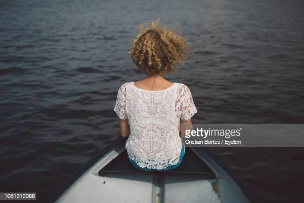Rear View Of Woman Sitting On Boat In Lake