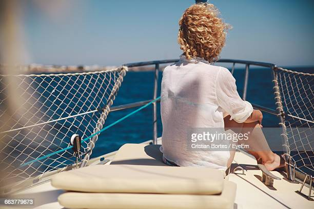 Rear View Of Woman Sitting On Boat Over Sea