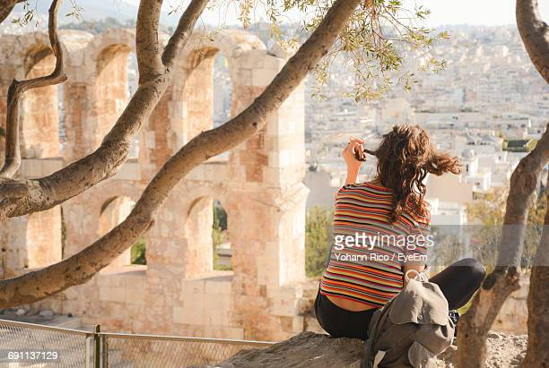 Rear View Of Woman Sitting On Branch At Acropolis Of Athens
