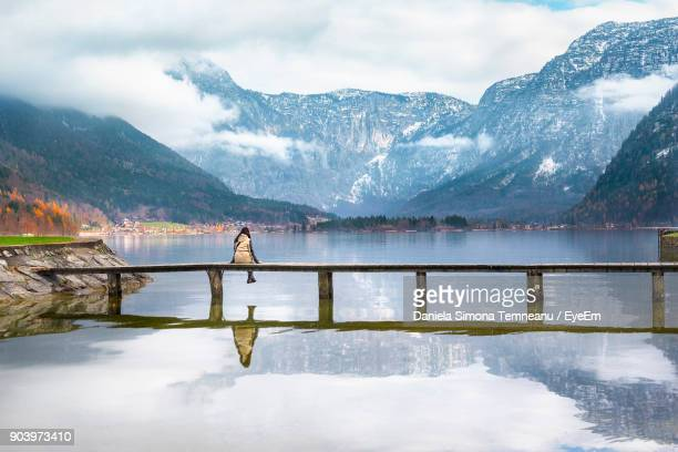 rear view of woman sitting on bridge over hallstatter see against mountains in hallstatt - hallstatter see stock pictures, royalty-free photos & images