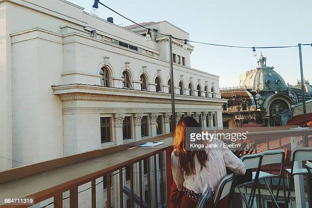 rear view of woman sitting on chair at building terrace in city - bucharest stock pictures, royalty-free photos & images