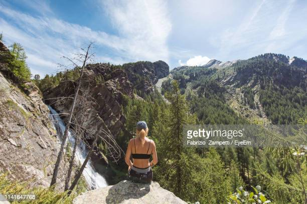 rear view of woman sitting on cliff against mountain range - fabrizio zampetti foto e immagini stock