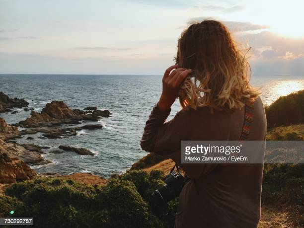rear view of woman sitting on cliff against sea - mid length hair stock pictures, royalty-free photos & images