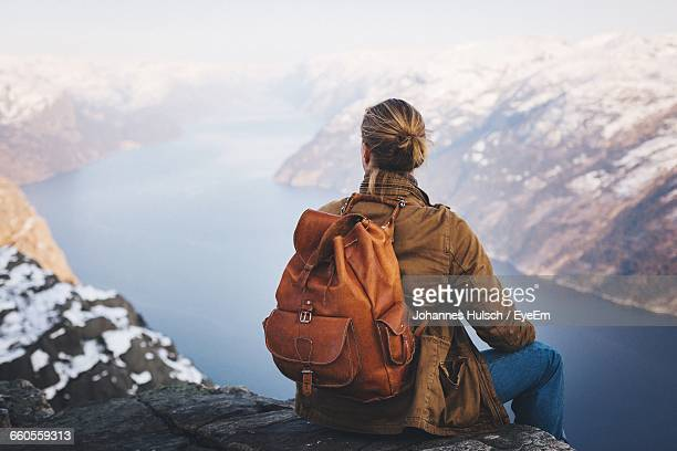 rear view of woman sitting on cliff in front of river - ローガラン県 ストックフォトと画像