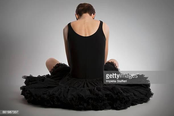 rear view of woman sitting on floor wearing black tutu - コクチョウ ストックフォトと画像