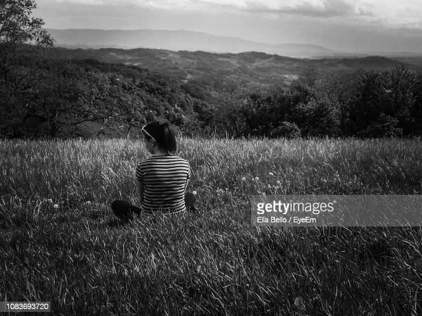 rear view of woman sitting on grassy field - ella bello stock-fotos und bilder
