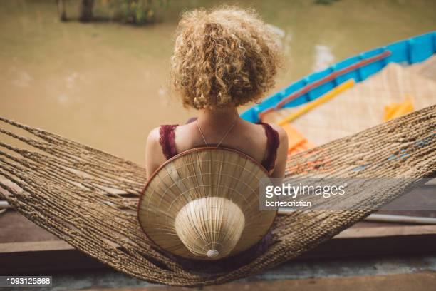 rear view of woman sitting on hammock over river - bortes imagens e fotografias de stock
