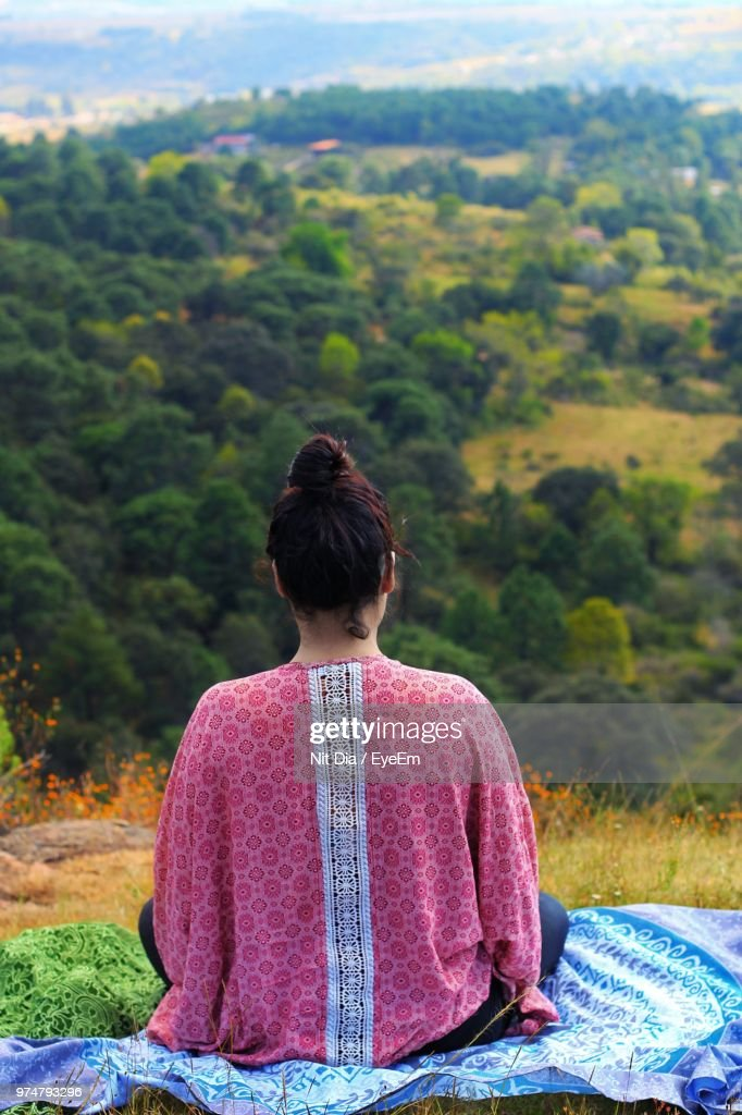 Rear View Of Woman Sitting On Hill : Stock Photo