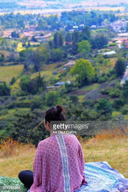 Rear View Of Woman Sitting On Hill