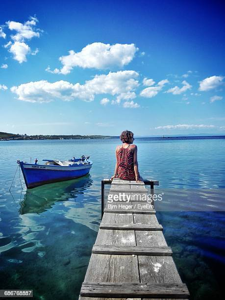 Rear View Of Woman Sitting On Jetty In Sea Against Sky