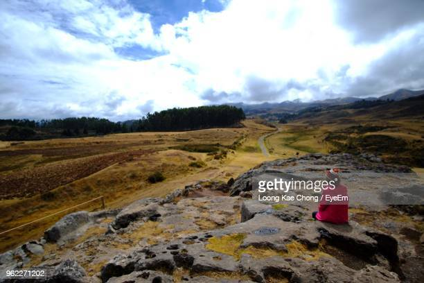 Rear View Of Woman Sitting On Landscape Against Cloudy Sky