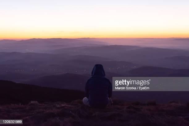 rear view of woman sitting on landscape against sky at sunset - babia góra mountain stock pictures, royalty-free photos & images