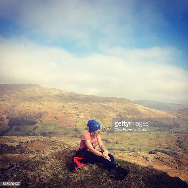 rear view of woman sitting on landscape against sky - ambleside stock photos and pictures