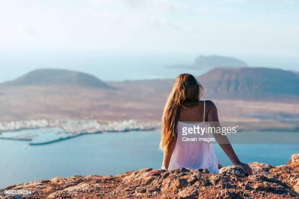 rear view of woman sitting on mountain against island - islas canarias fotografías e imágenes de stock