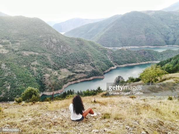 rear view of woman sitting on mountain by lake - albania stock-fotos und bilder