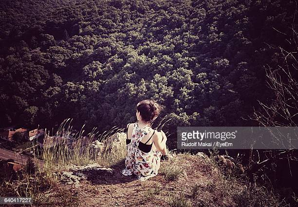 Rear View Of Woman Sitting On Mountain With Trees In Background