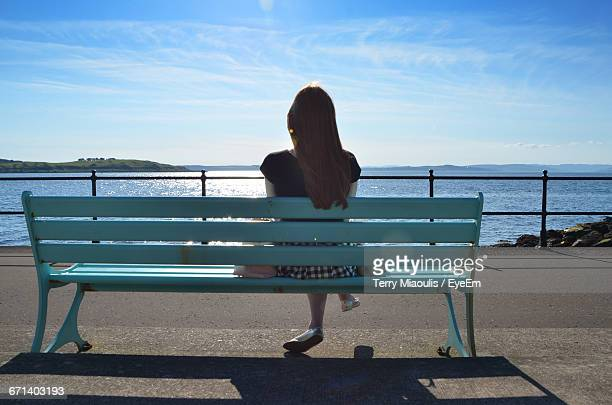 Rear View Of Woman Sitting On Park Bench Against River And Sky During Sunny Day