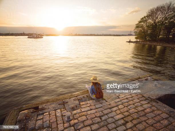Rear View Of Woman Sitting On Pier During Sunset