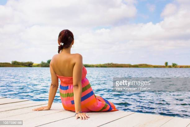 rear view of woman sitting on pier over lake against sky - strapless dress stock pictures, royalty-free photos & images