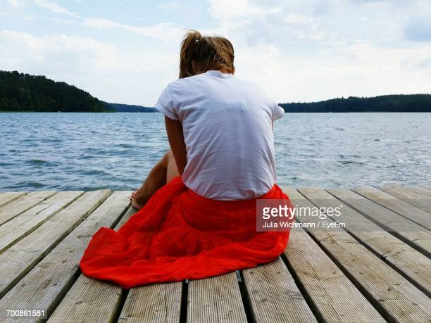 Rear View Of Woman Sitting On Pier Over Lake Against Sky