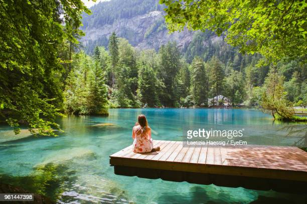 rear view of woman sitting on pier over lake at forest - switzerland stock pictures, royalty-free photos & images