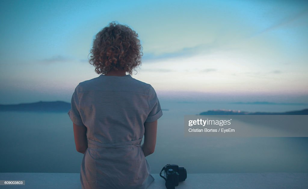 Rear View Of Woman Sitting On Retaining Wall Against Sea : Stock Photo