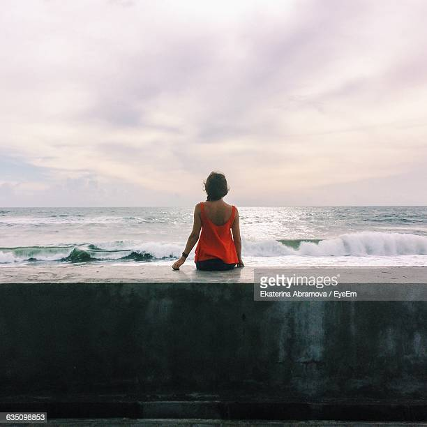 rear view of woman sitting on retaining wall by sea against cloudy sky - retaining wall stock pictures, royalty-free photos & images