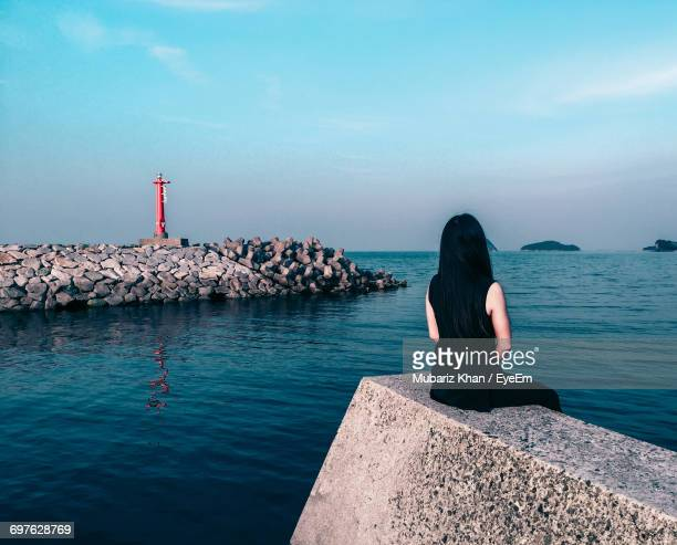 Rear View Of Woman Sitting On Retaining Wall By Sea Against Sky