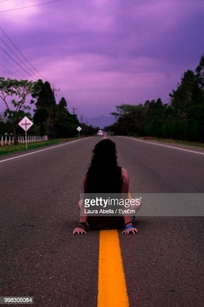 Rear View Of Woman Sitting On Road Against Cloudy Sky