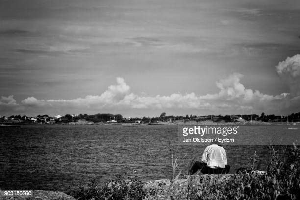 Rear View Of Woman Sitting On Rock Against Lake