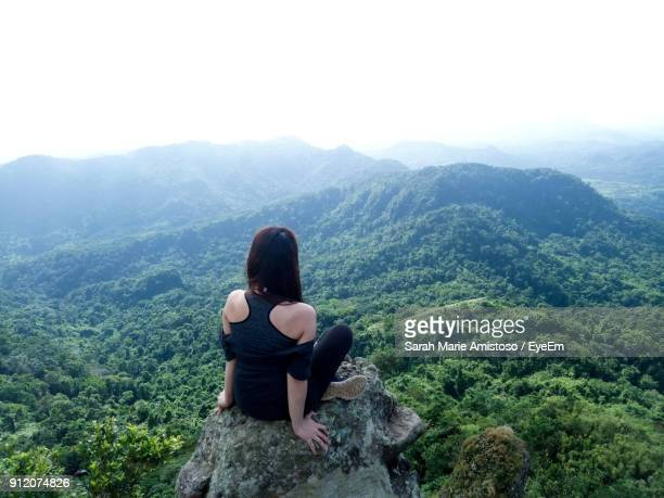 Rear View Of Woman Sitting On Rock Against Landscape