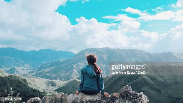 rear view of woman sitting on rock against mountains during winter - paisajes de filipinas fotografías e imágenes de stock