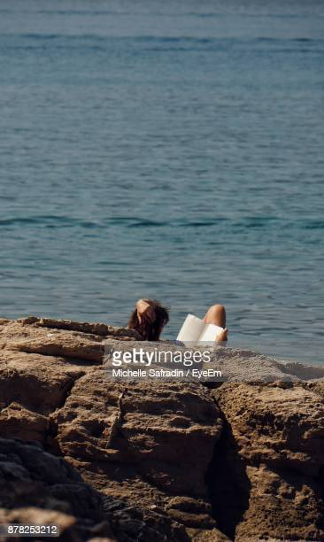 Rear View Of Woman Sitting On Rock Against Sea At Beach