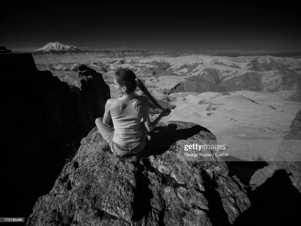Rear View Of Woman Sitting On Rock Against Sky : Photo