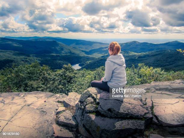 Rear View Of Woman Sitting On Rock Against Sky