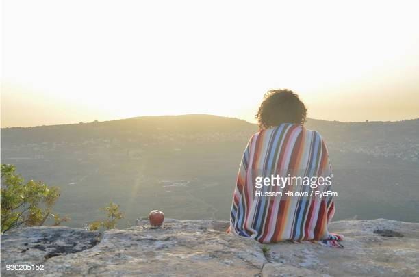 rear view of woman sitting on rock against sky - beirut stock pictures, royalty-free photos & images