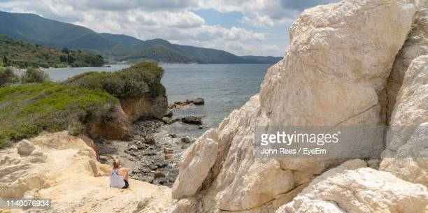 Rear View Of Woman Sitting On Rock At Beach