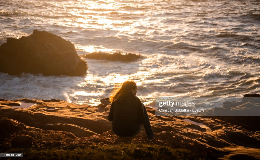 Rear View Of Woman Sitting On Rock At Beach : Stock-Foto