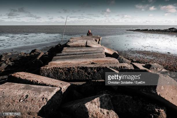 rear view of woman sitting on rock at beach - christian soldatke stock pictures, royalty-free photos & images