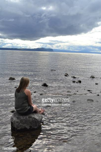 rear view of woman sitting on rock at shore against cloudy sky - corinne paradis photos et images de collection