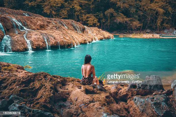 rear view of woman sitting on rock by semuc champey lake in guatemala - guatemala stock pictures, royalty-free photos & images