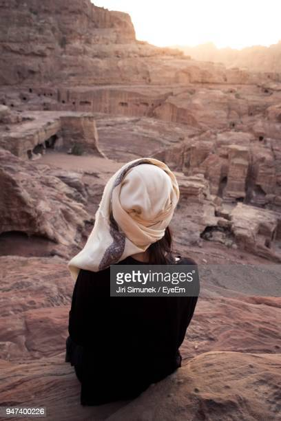 Rear View Of Woman Sitting On Rock Formation Against Sky