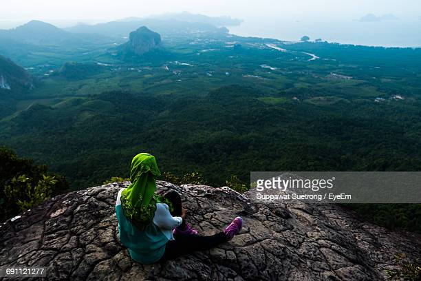 Rear View Of Woman Sitting On Rock Formation While Looking At Landscape