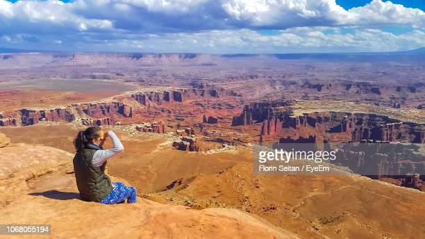 rear view of woman sitting on rock while looking at canyon against cloudy sky - florin seitan stock pictures, royalty-free photos & images