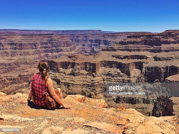Rear View Of Woman Sitting On Rocky Mountain At Grand Canyon
