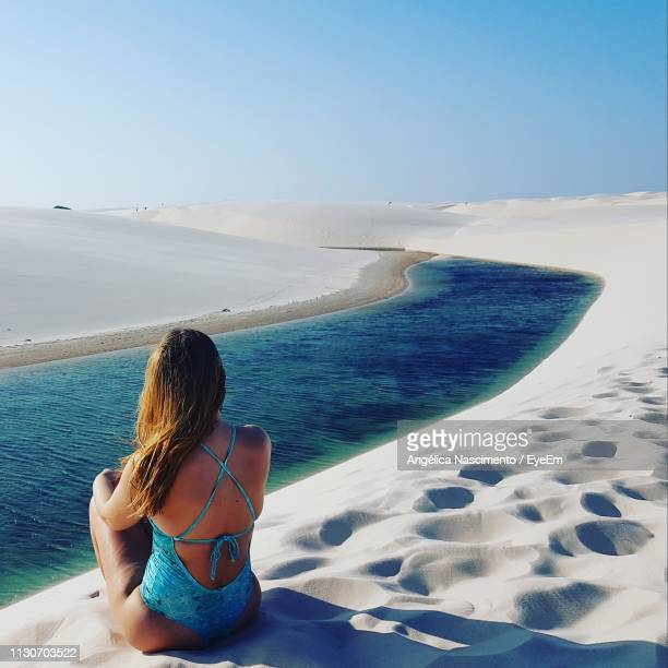 rear view of woman sitting on sand by river - barreirinhas stock pictures, royalty-free photos & images