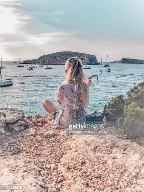 rear view of woman sitting on shore at beach against cloudy sky - insel ibiza stock-fotos und bilder