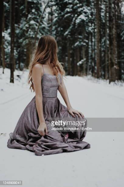 rear view of woman sitting on snow covered land - prom dress stock pictures, royalty-free photos & images